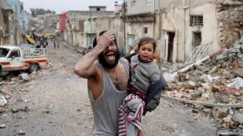 A desperate man with a young girl in his arms, walking amongst the ruins of the Old City of Mosul.