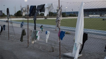 Clothes hanging on barbed wire fence at the Elliniko refugee camp