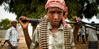 A young Al-Shabab soldier poses with his weapon. Many of the young Somalian boys recruited or abducted into the terrorist group are promised an education and money for their families.