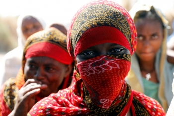 An Ethiopian woman wearing a red niqab and looking at the camera Credits: