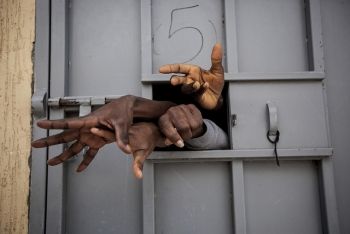 Sub-Saharan migrants and refugees begging for their release in a detention center in Surman, Libya