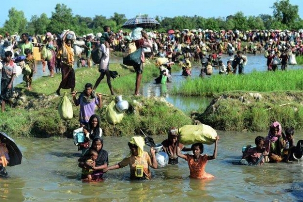 Rohingya refugee crossing a shallow canal