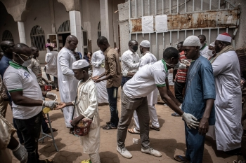 Security Personnel scan and offer hand sanitizer to worshippers attending a mosque in Burkina Faso