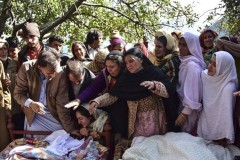 Relatives and friends mourn next to bodies of victims in cross border shelling in Pakistan's Neelum valley