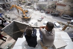 Two Palestinenan boys look down over their demolished housing complex