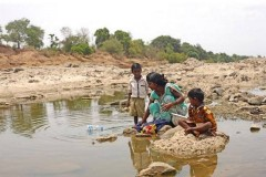 Mother and her children wash in river in Maharashtra, India