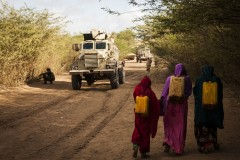 Women carrying water next to soldiers searching for IEDs