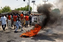 Protesters in Maiduguri blocking the road and standing by a burning tire while demanding the end of the CJTF militia on 30 June 2019