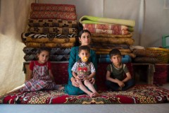 A young Yazidi woman sits with her three children inside a tent in Sharya camp in northern Iraq.