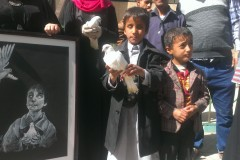 A blind Yemenis child carries a dove in a protest against an attack in the capital