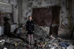 A pupil in eastern Ukraine stands amid the wreckage of her conflict-damaged schoolroom